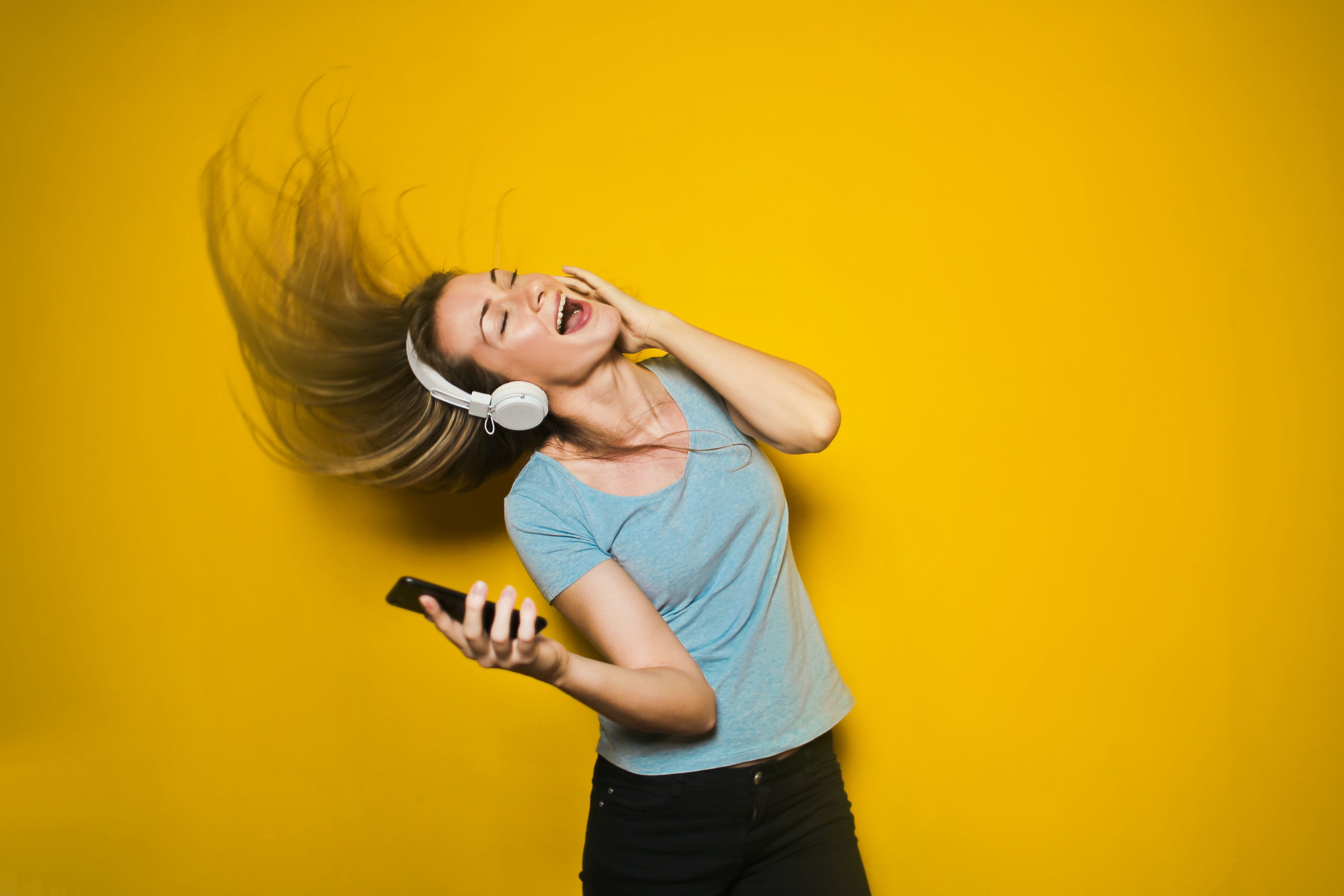 extrovert employees - girl dancing with earphones in with a yellow background